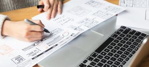 Person sketching a redesign for a website