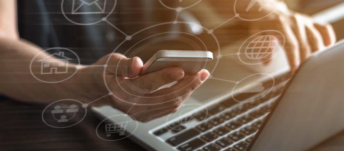 Social media icons circling phone and laptop